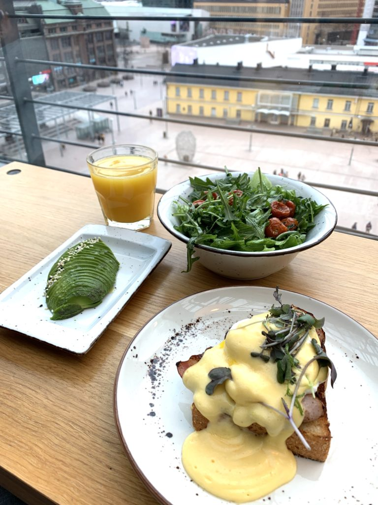 Photo of breakfast at Story Kamppi. Eggs benedict, side salad, avocado, orange juice.
